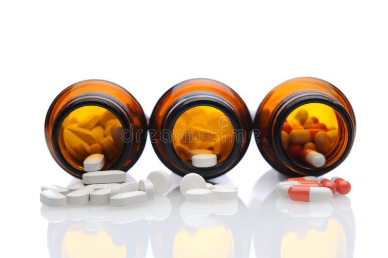 Garrafas da medicina com os comprimidos que derramam para fora fotografia de stock royalty free