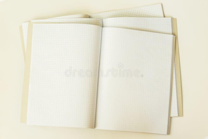 Close-up de três grandes cadernos limpos e vazios abertos em uma gaiola, vista superior, fundo, textura Lugar para o texto, conce fotos de stock