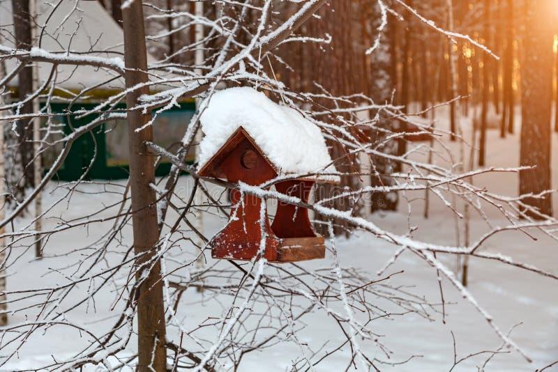 Close-up de um alimentador de madeira do pássaro do aviário coberto com uma grande camada de neve em um dia de inverno claro em u fotografia de stock