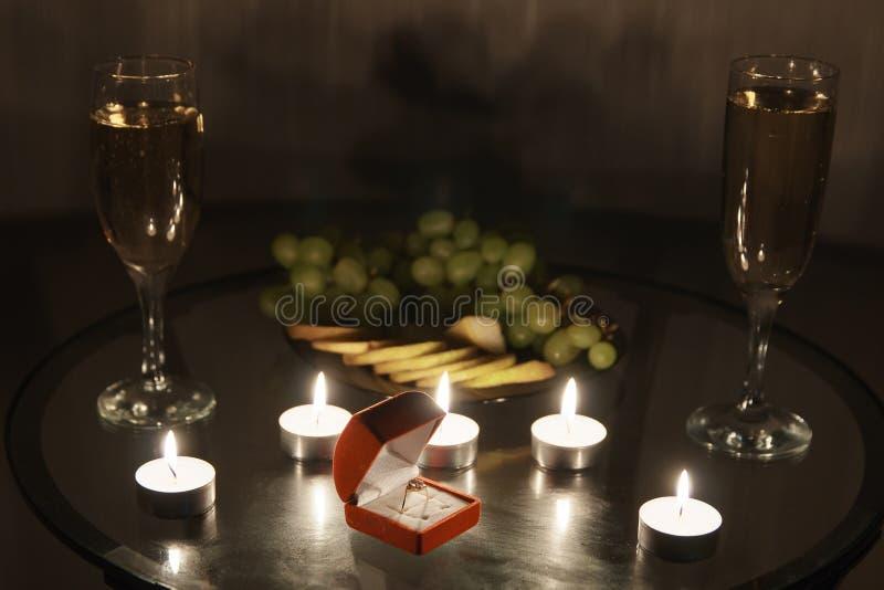 Close-up de um anel em uma caixa vermelha contra um fundo de velas ardentes foto de stock