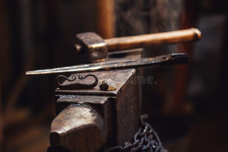Close up de um batente do ferreiro com um martelo, os tenazes de brasa, o firesteel e o sílex imagem de stock