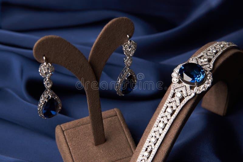 Close-up de um bracelete bonito e de brincos da platina imagem de stock royalty free