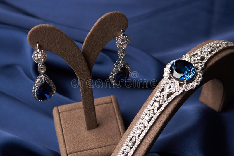 Close-up de um bracelete bonito e de brincos da platina imagens de stock