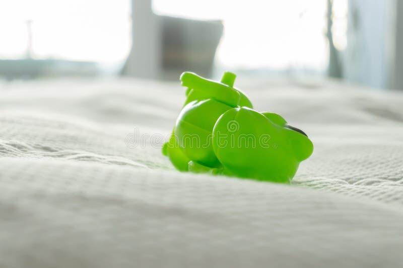 Close up de um brinquedo do dinossauro verde em uma cama com folhas brancas e fundamento branco, descrevendo a vida parenting e a imagem de stock royalty free