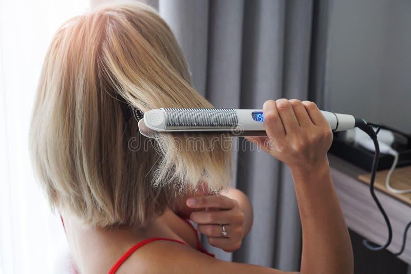 Close-up de um cabeleireiro que endireita o cabelo marrom longo com hai fotos de stock