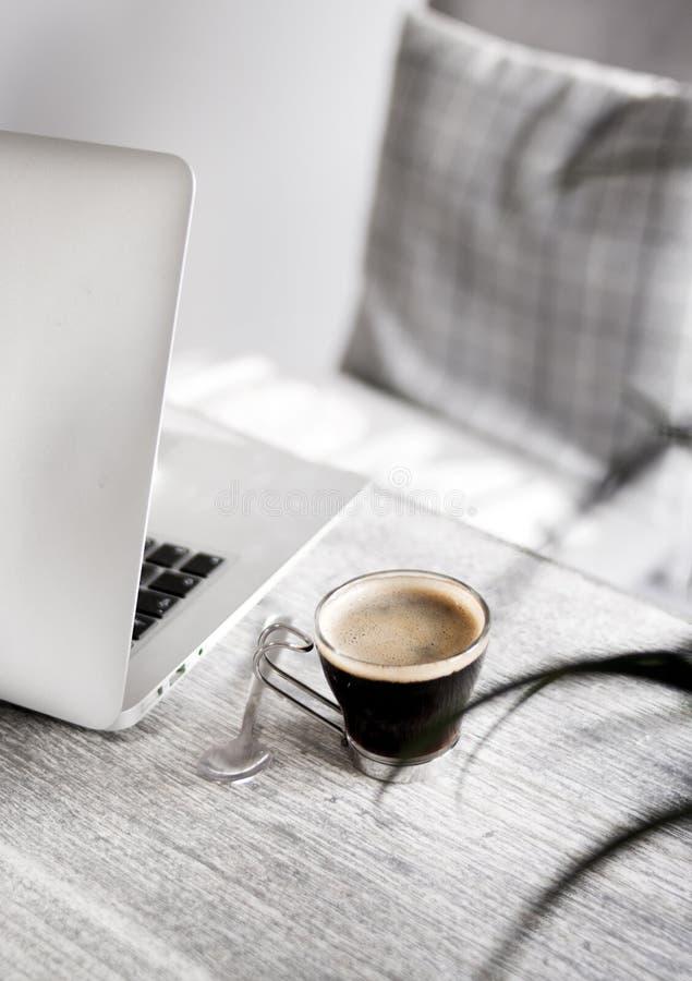 Close up de um café em uma tabela com uma colher e um portátil no lado fotos de stock royalty free
