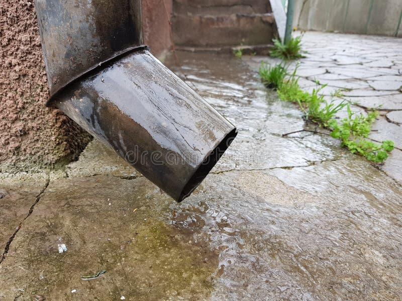 Close-up de um cano e de um assoalho molhado de um pátio rural imagens de stock royalty free