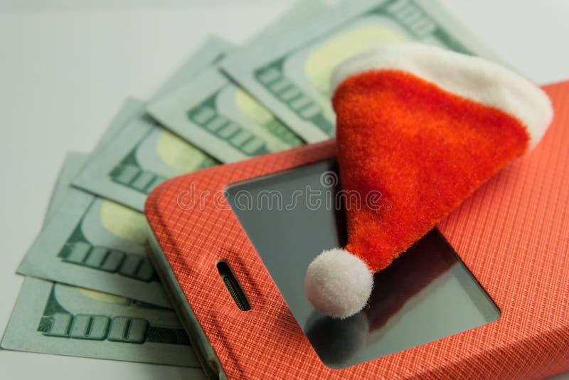 Close-up de um chapéu da lembrança de Santa Claus que encontra-se em um smartphone em uma caixa vermelha na perspectiva de cinco  imagem de stock royalty free