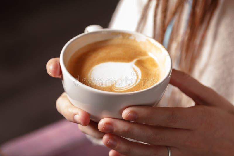 Close-up de um copo branco do café quente da arte do latte com uma forma do coração nas mãos de uma moça Abrandamento, caneca de  imagens de stock