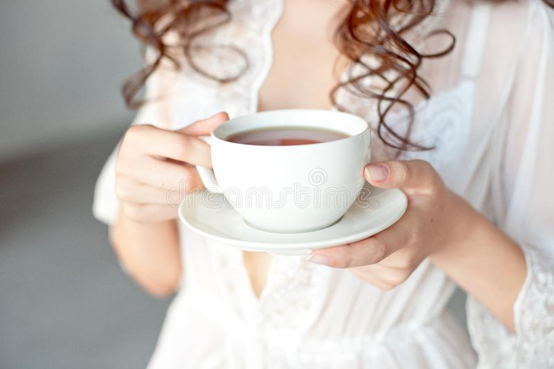 Close-up de um copo branco do caf? quente da arte do latte com uma forma do cora??o nas m?os de uma mo?a foto de stock
