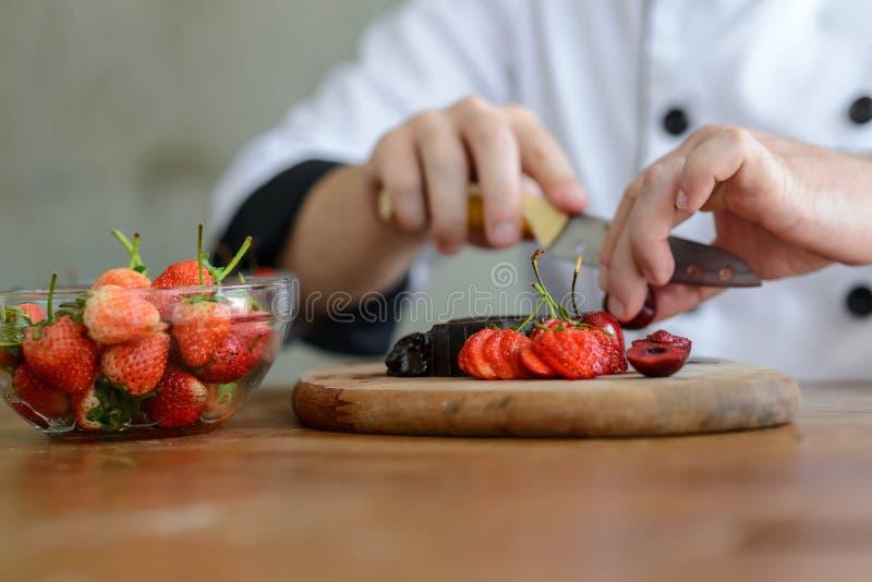 Close up de um cozinheiro chefe de pastelaria que decora a sobremesa com a morango em t fotos de stock