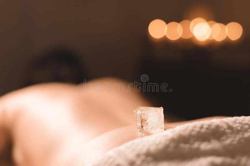Close-up de um cubo de gelo transparente que encontra-se na parte traseira mais baixa de uma moça que encontra-se em um sofá para fotos de stock
