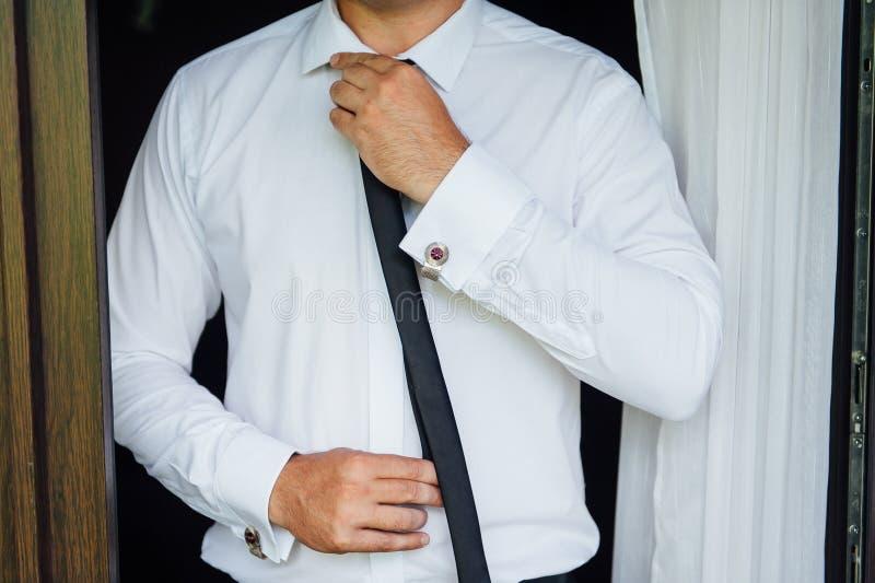Close-up de um homem em um tux que fixa seu botão de punho do vintage botão de punho do laço do noivo imagens de stock royalty free
