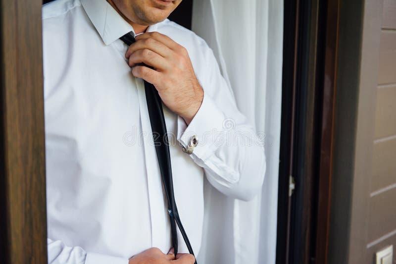 Close-up de um homem em um tux que fixa seu botão de punho do vintage botão de punho do laço do noivo imagem de stock royalty free