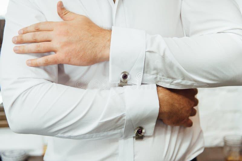 Close-up de um homem em um tux que fixa seu botão de punho do vintage botão de punho do laço do noivo fotos de stock