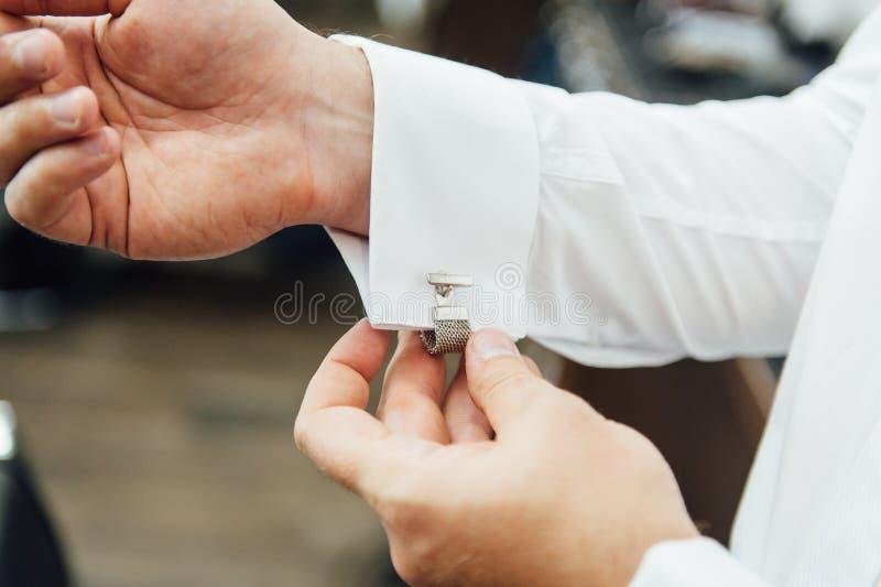 Close-up de um homem em um tux que fixa seu botão de punho do vintage botão de punho do laço do noivo imagens de stock