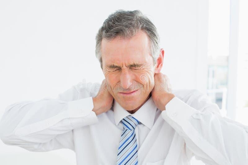 Close up de um homem maduro que sofre da dor de pescoço imagens de stock royalty free
