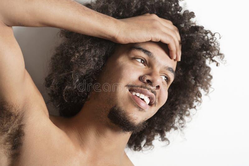 Close-up de um homem novo feliz com mão na cabeça sobre o fundo branco imagem de stock