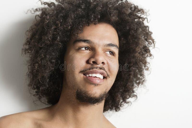 Close-up de um homem novo feliz com o cabelo encaracolado que olha afastado sobre o fundo branco imagens de stock royalty free