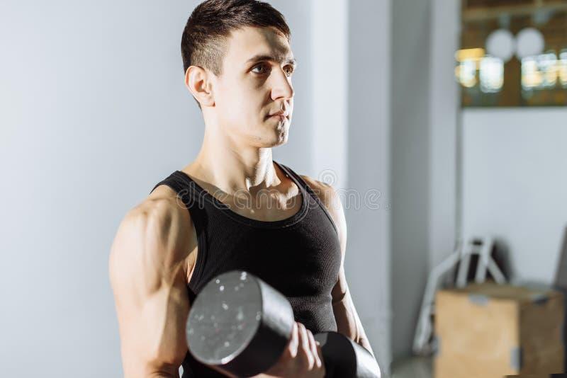 Close up de um homem novo muscular que levanta peso no gym imagens de stock royalty free