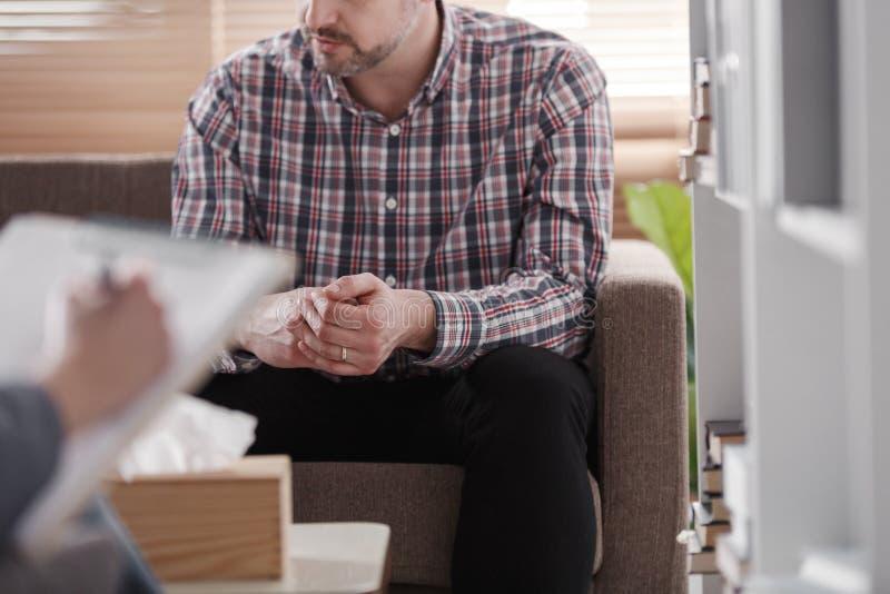 Close-up de um homem que senta-se em um sofá durante a consulta marital imagem de stock