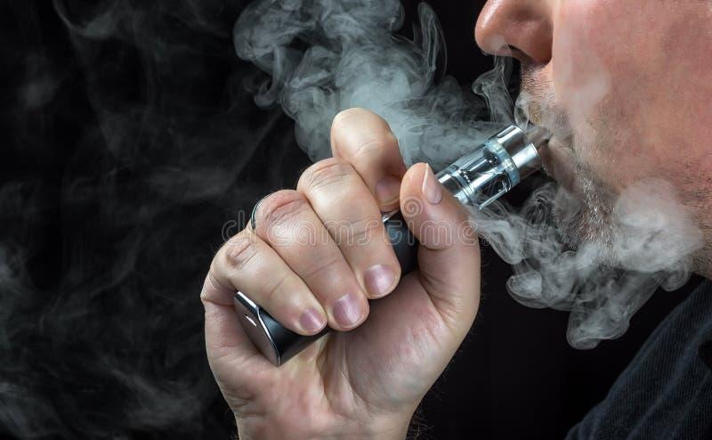 Close-up de um homem que vaping um cigarro eletrônico foto de stock royalty free