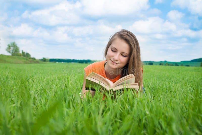 Close up de um livro de leitura bonito da jovem mulher no parque fotos de stock royalty free