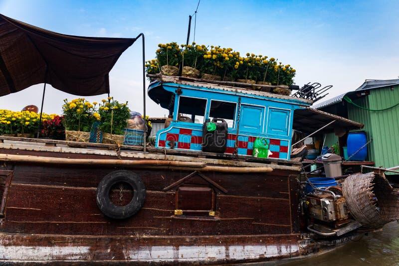Close-up de um marrom e de um barco azul ou sampana que leva flores amarelas e vermelhas para a celebração do ano novo de Tet, de fotos de stock royalty free