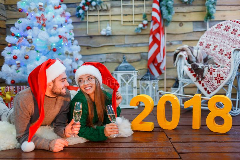 Close-up de um par novo em chapéus de Santa, guardando vidros com champanhe nas mãos, encontrando-se no assoalho foto de stock royalty free
