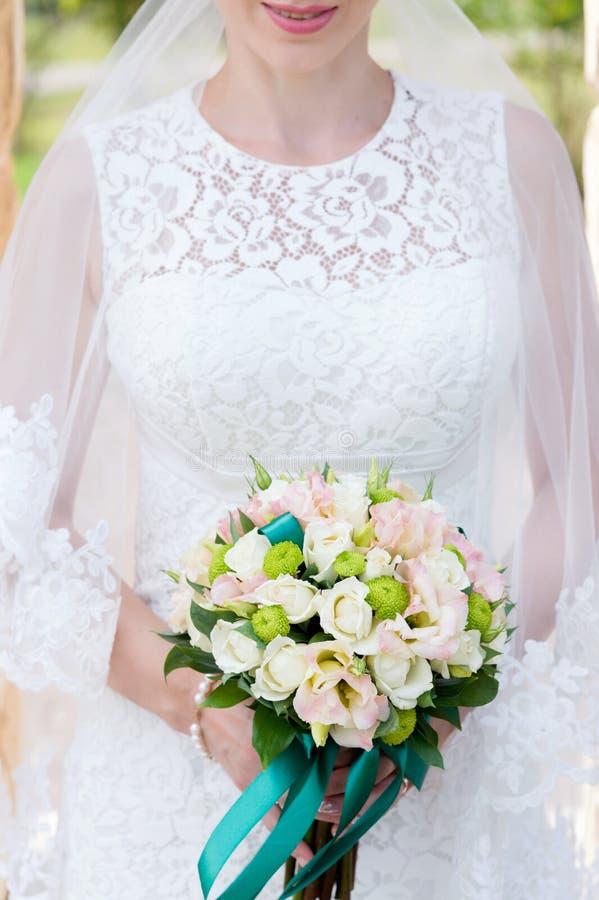 Close-up de um ramalhete nupcial perto da noiva em seus braços Caixa e ramalhete de Chin no quadro fotografia de stock royalty free