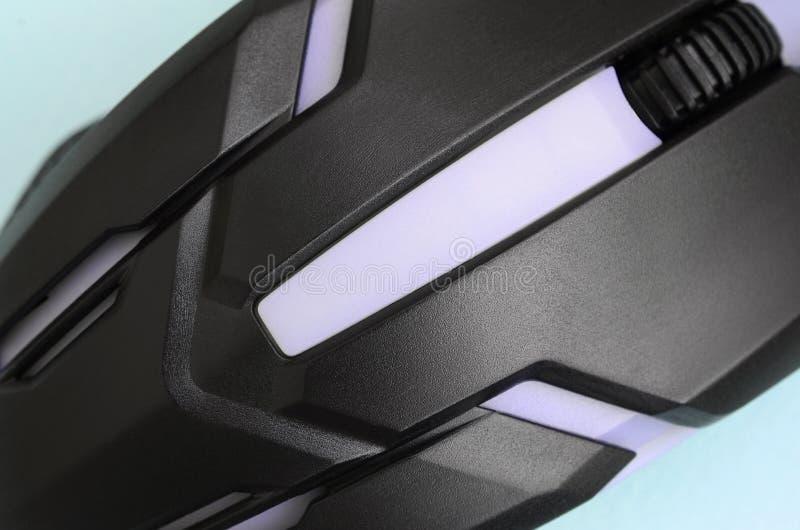 Close up de um rato ótico do jogo preto em um fundo azul fotografia de stock