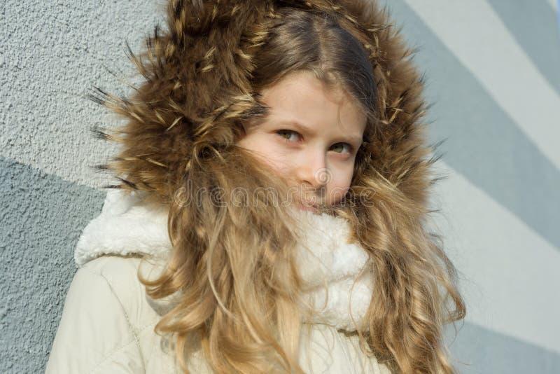 Close-up de um retrato exterior do inverno da criança, menina loura com cabelo encaracolado de 7,8 anos na capa da pele fotos de stock royalty free