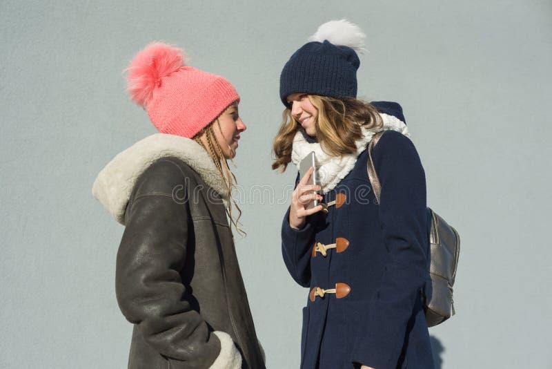 Close-up de um retrato exterior do inverno de dois estudantes dos adolescentes em um perfil que sorriem e que falam imagem de stock royalty free