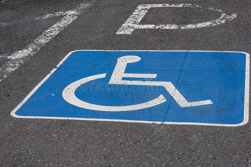 Close up de um sinal azul da desvantagem pintado na rua do asfalto perto de um parque fotografia de stock royalty free