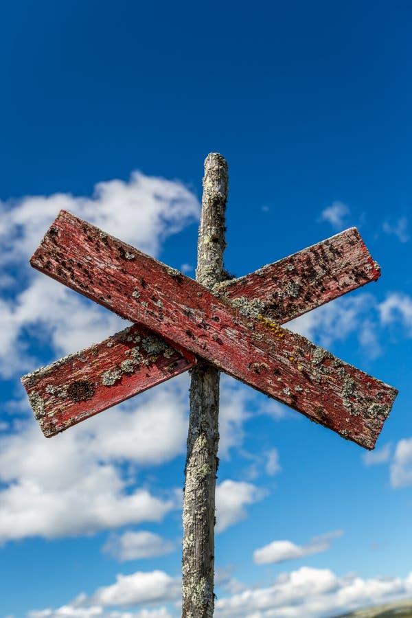 Close up de um sinal de madeira gasto velho vermelho da fuga do passeio Cruz exterior contra o c?u azul fotografia de stock royalty free