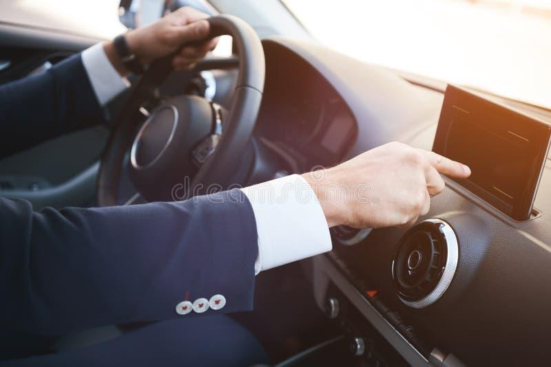 Close-up de um smartphone preto tocante da tela da mão do homem em um painel fotografia de stock royalty free