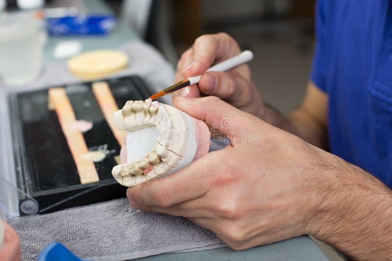 Close up de um técnico dental que aplica a porcelana a um molde fotos de stock