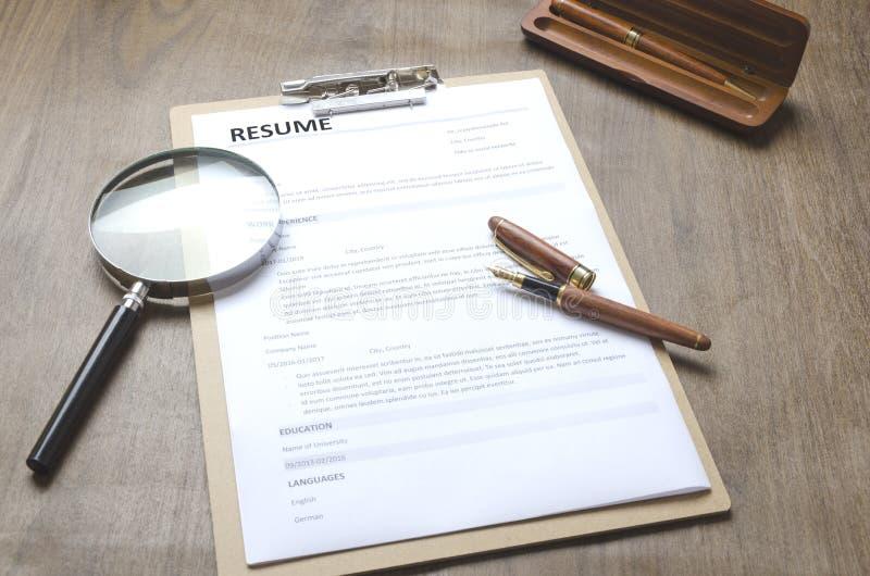 Close up de uma aplicação do resumo, prancheta, pena, lente de aumento na tabela de madeira, pessoa novo dealuguer de trabalho Co imagens de stock