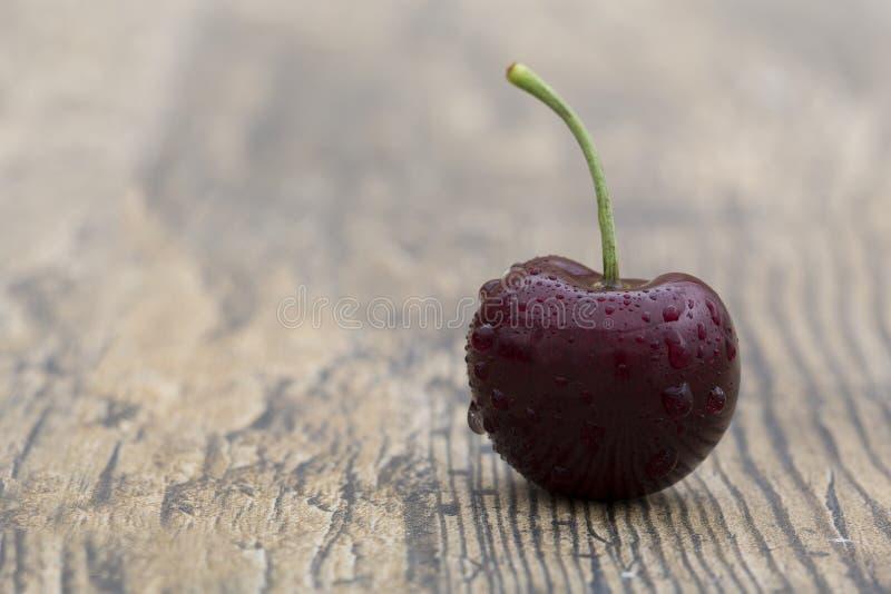 Close-up de uma cereja em um fundo de madeira marrom fotos de stock royalty free