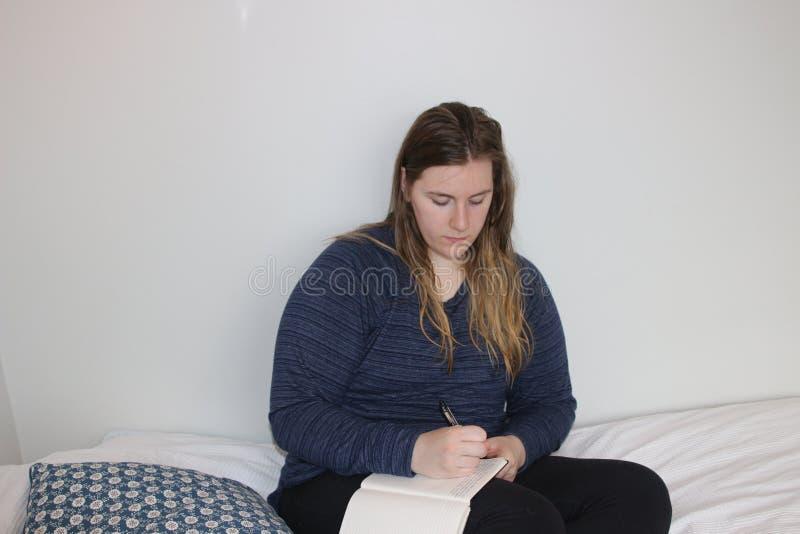 Close-up de uma escrita da menina em um caderno imagem de stock