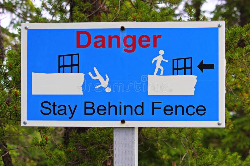 Close up de uma estada do perigo atrás do sinal da cerca foto de stock royalty free