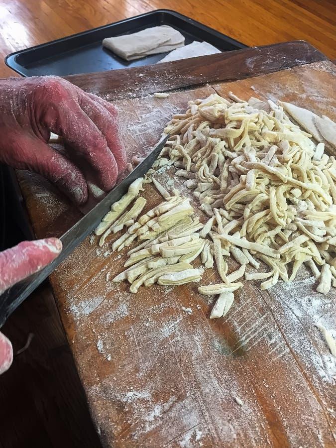 Close up de uma faca que corta acima macarronetes de ovo caseiros foto de stock royalty free