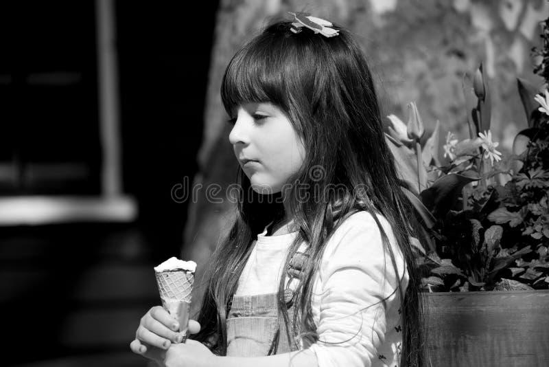 Close up de uma foto preto e branco de 6 anos de retrato velho da criança da menina da criança pequena que anda ao longo da rua d foto de stock