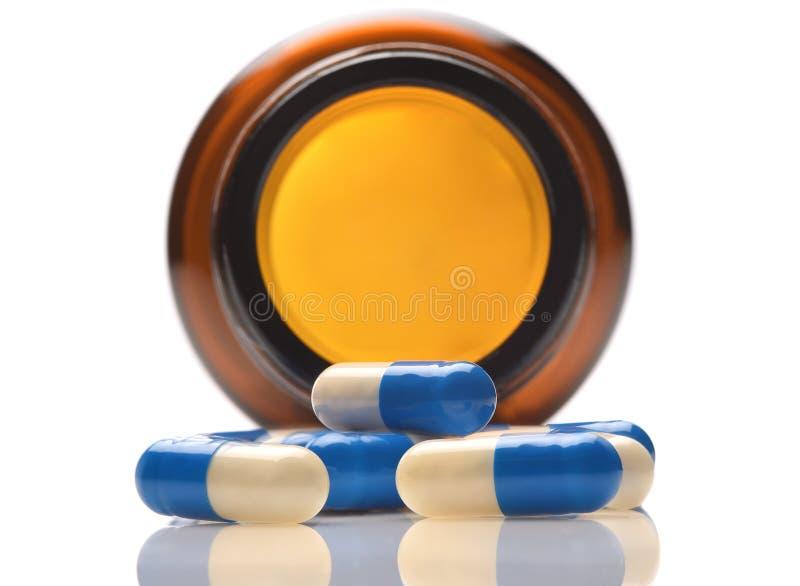 Close up de uma garrafa da prescrição em seu lado com as cápsulas do azul e do whiite que derramam para fora imagens de stock royalty free
