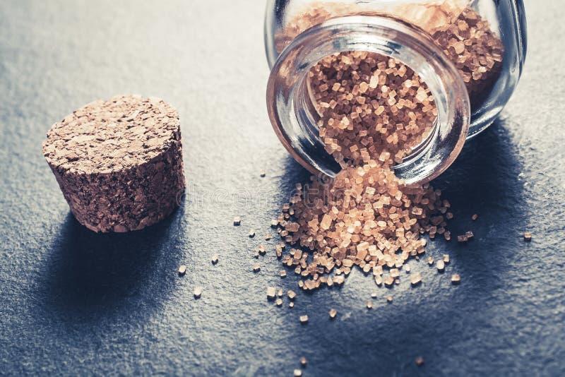 Close-up de uma garrafa de vidro virada com Brown derramado Sugar Next To cru Cork Stopper On Slate Stone imagens de stock
