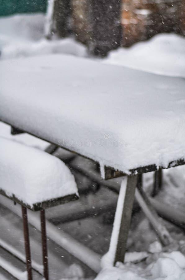 Close-up de uma jarda nevado com uma tabela e de bancos durante uma tempestade de neve e um blizzard foto de stock