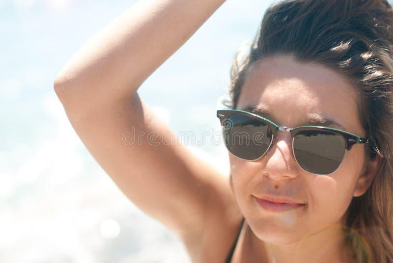 Close-up de uma jovem mulher com luz solar dos óculos de sol foto de stock