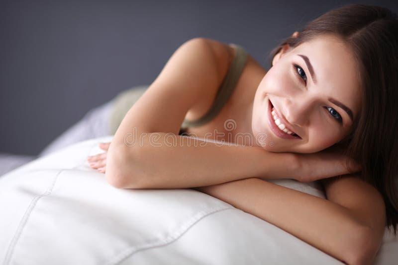 Close up de uma jovem mulher de sorriso que encontra-se no sofá imagens de stock royalty free