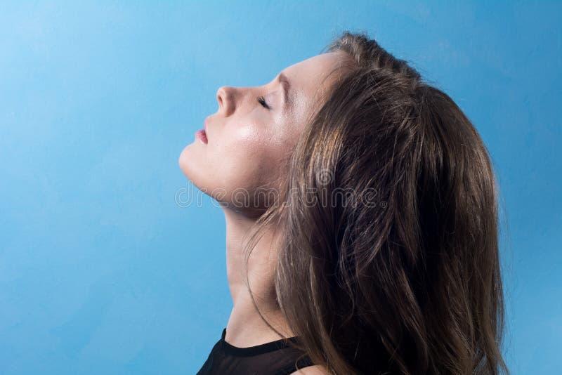 Close-up de uma jovem mulher no perfil com olhos fechados imagem de stock