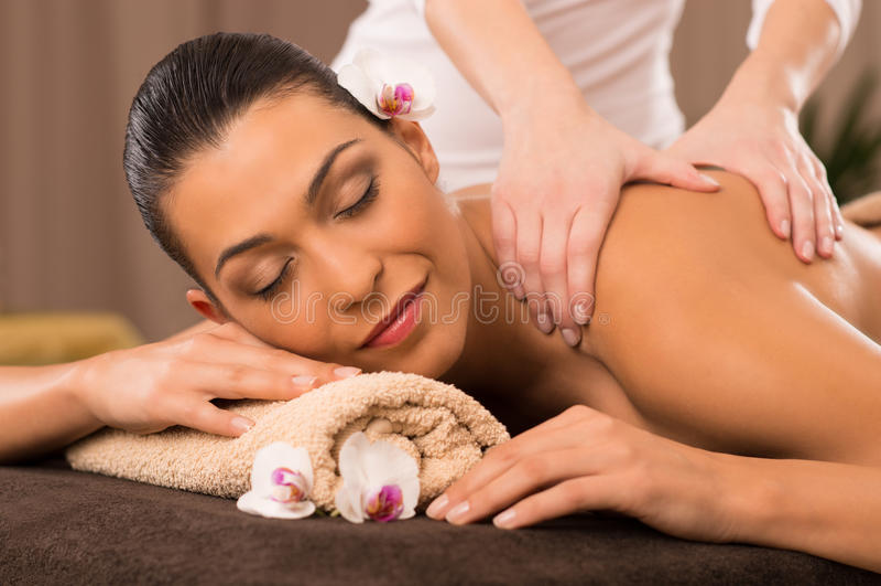 Close-up de uma jovem mulher que recebe a massagem traseira em termas imagens de stock